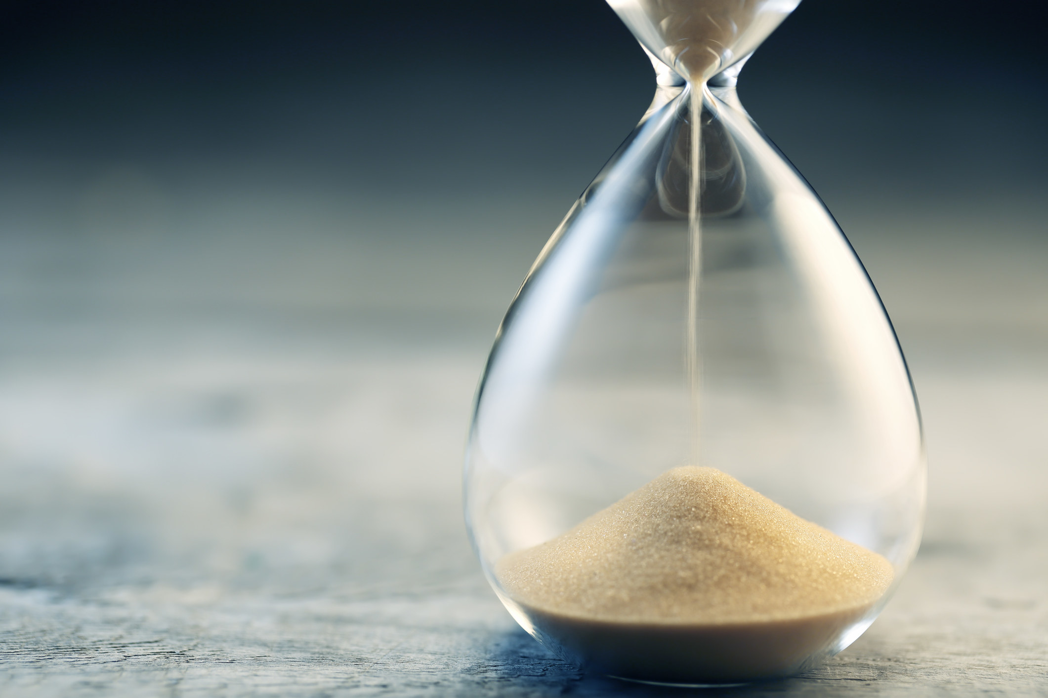 An hourglass of sand pouring slowly