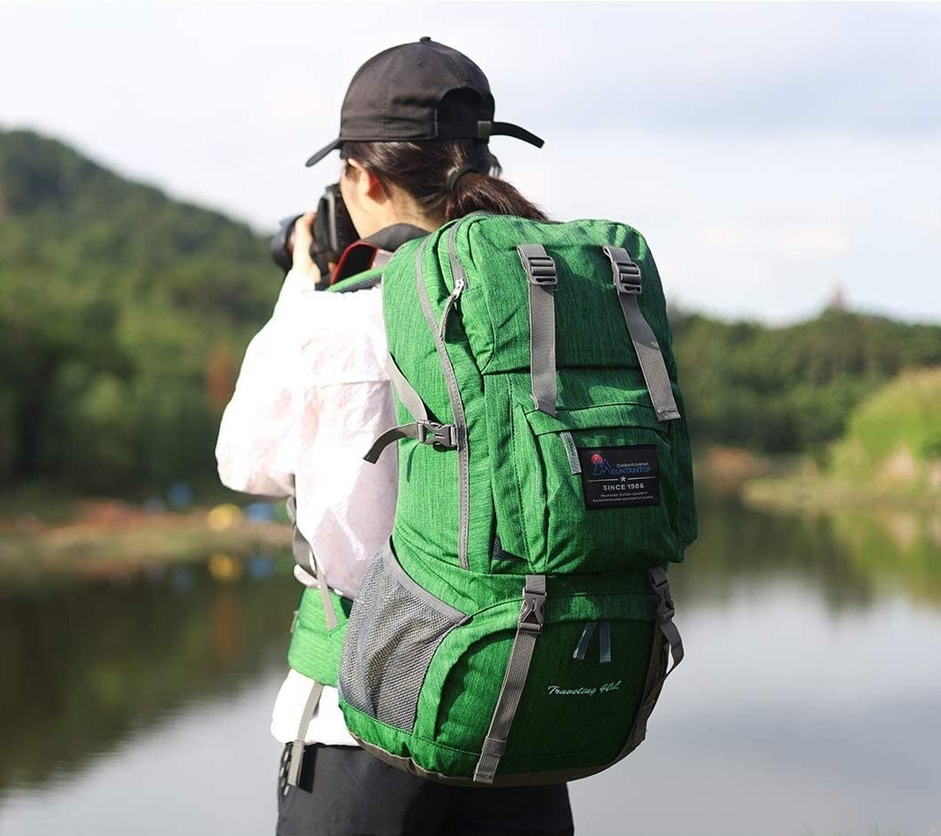 model wearing the backpack in green, which has waist strap as well as two shoulder straps