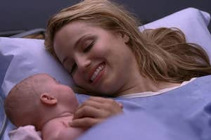 Quinn Fabray smiles down at her newborn daughter as they lay in a hospital bed.