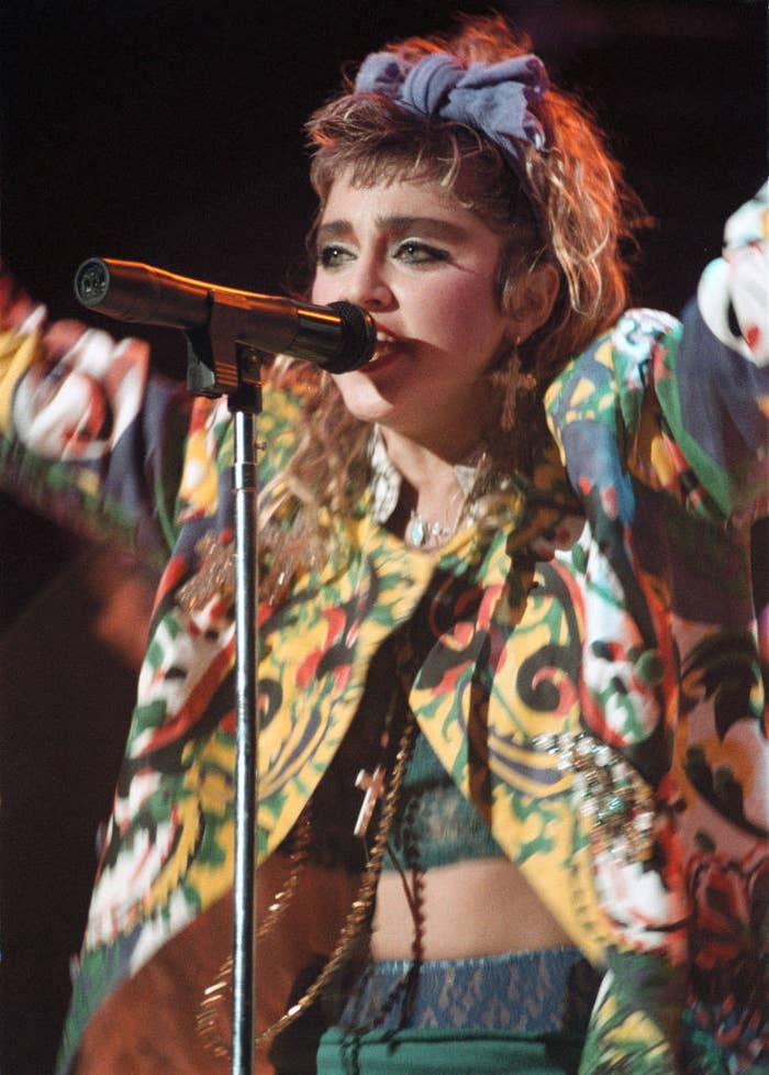 Madonna performing in concert in 1985 while wearing multiple chain necklaces, a colorful jacket, and big hair