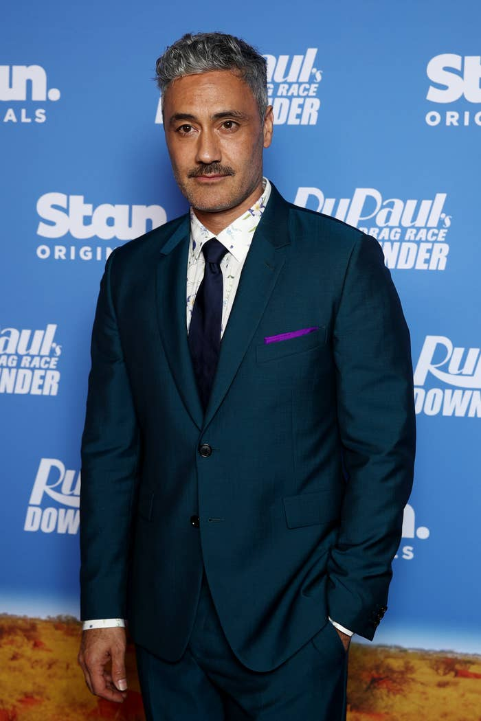 Taika Waititi on the red carpet in a suit and tie