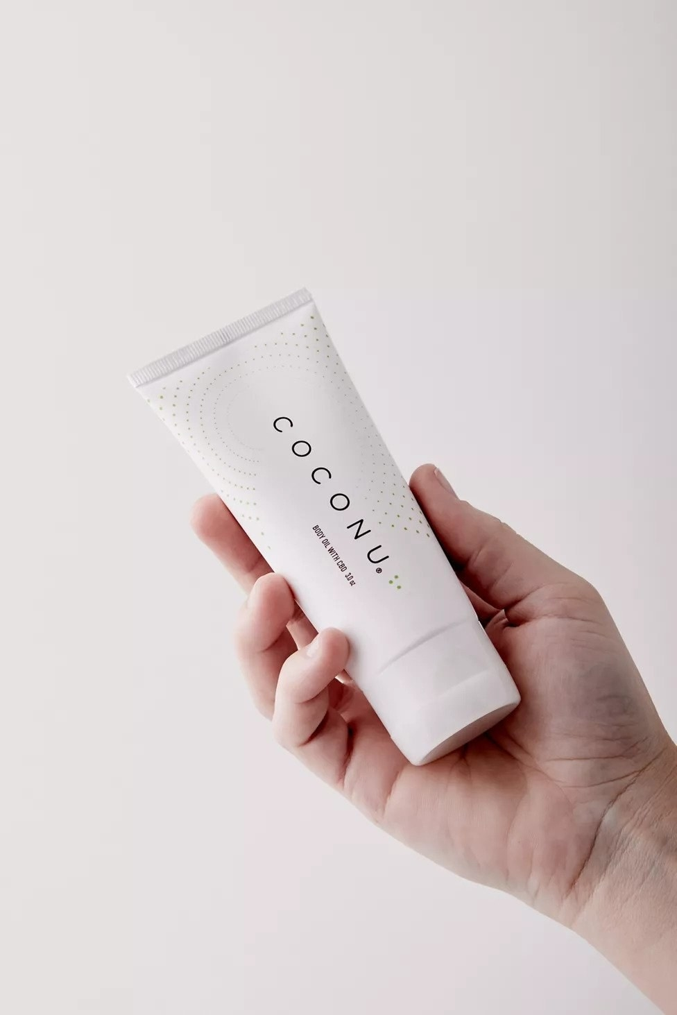 Model holding white tube of Coconu lubricant