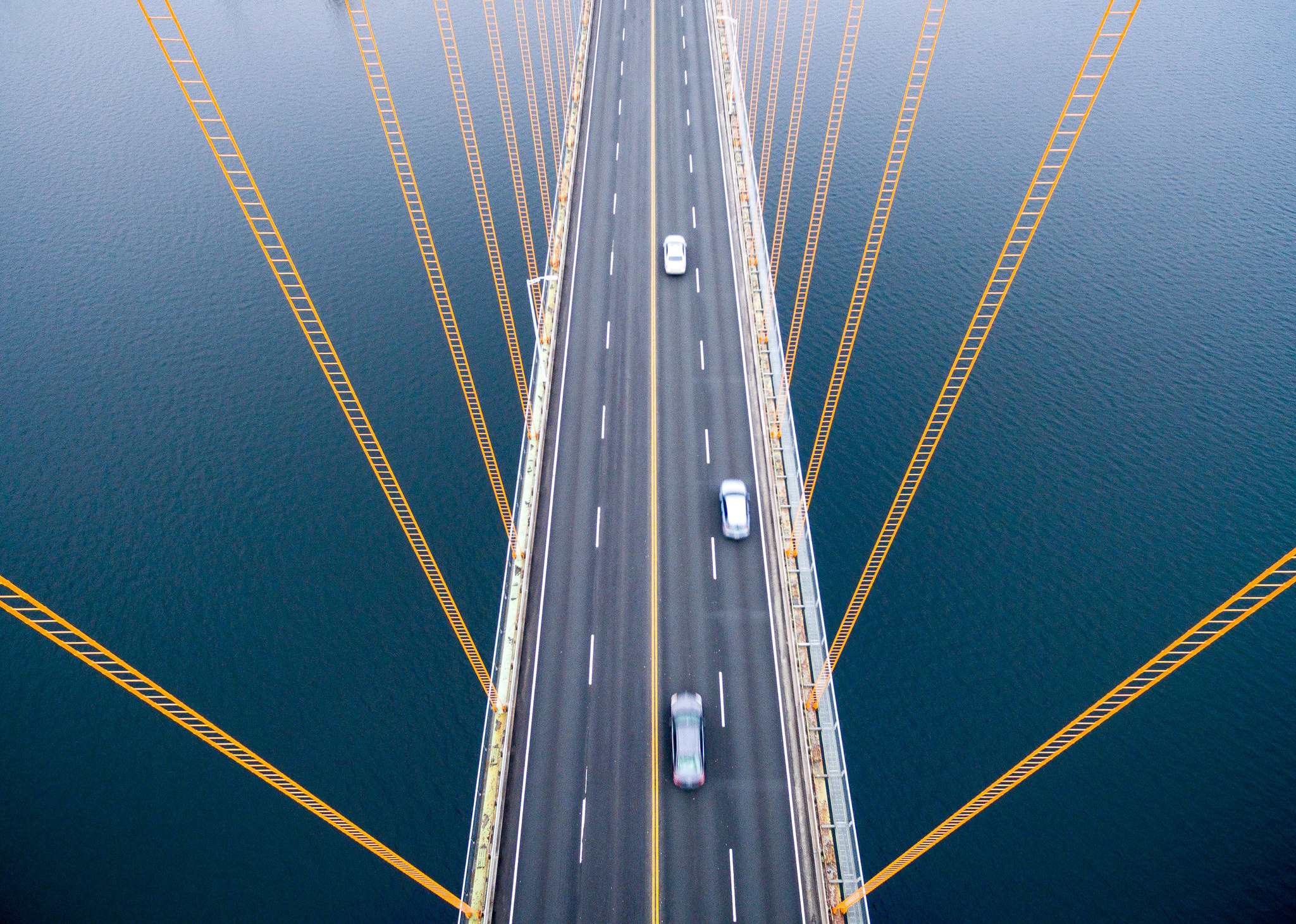 An above-head view of a long bridge with cars driving over it