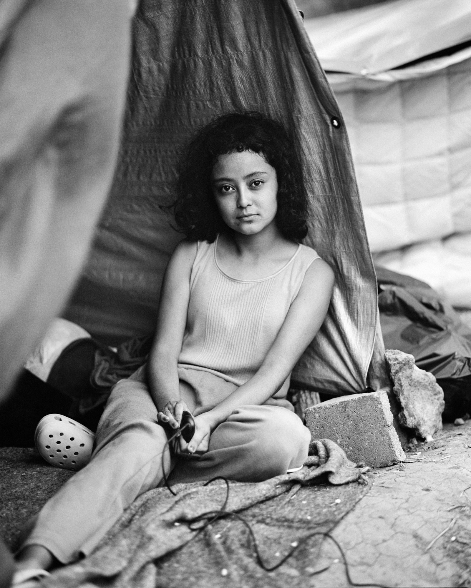 A girl in a makeshift tent uses a timer to takes a self-portrait at an informal migrant camp