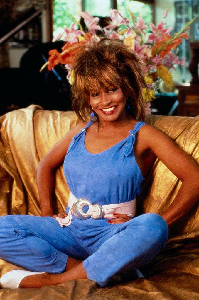 Tina Turner happily sitting on a sofa