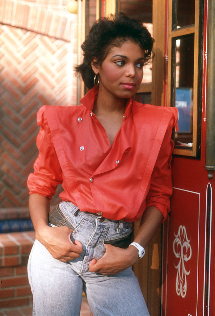 Janet Jackson poses for a portrait wearing jeans and a blouse with pointed shoulders in 1985