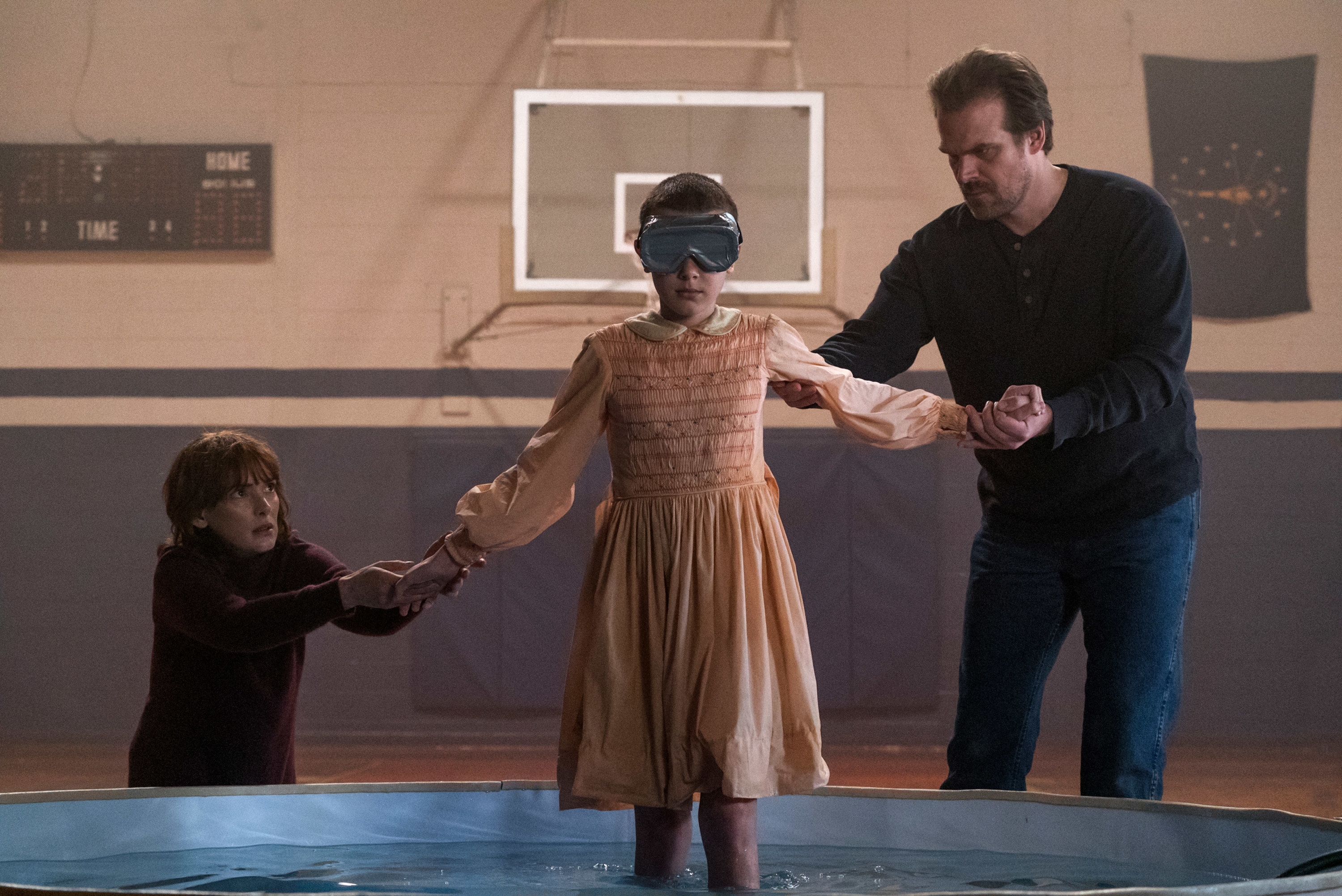 Joyce Byers and Hopper help Eleven into the saltwater pool in season 1