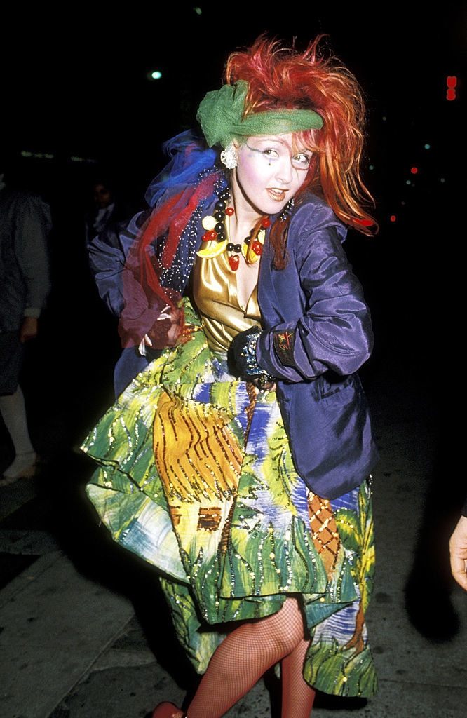 Cyndi Lauper at the 26th Grammy awards wearing a very colorful dress, plastic fruit necklace, and assorted colorful accessories
