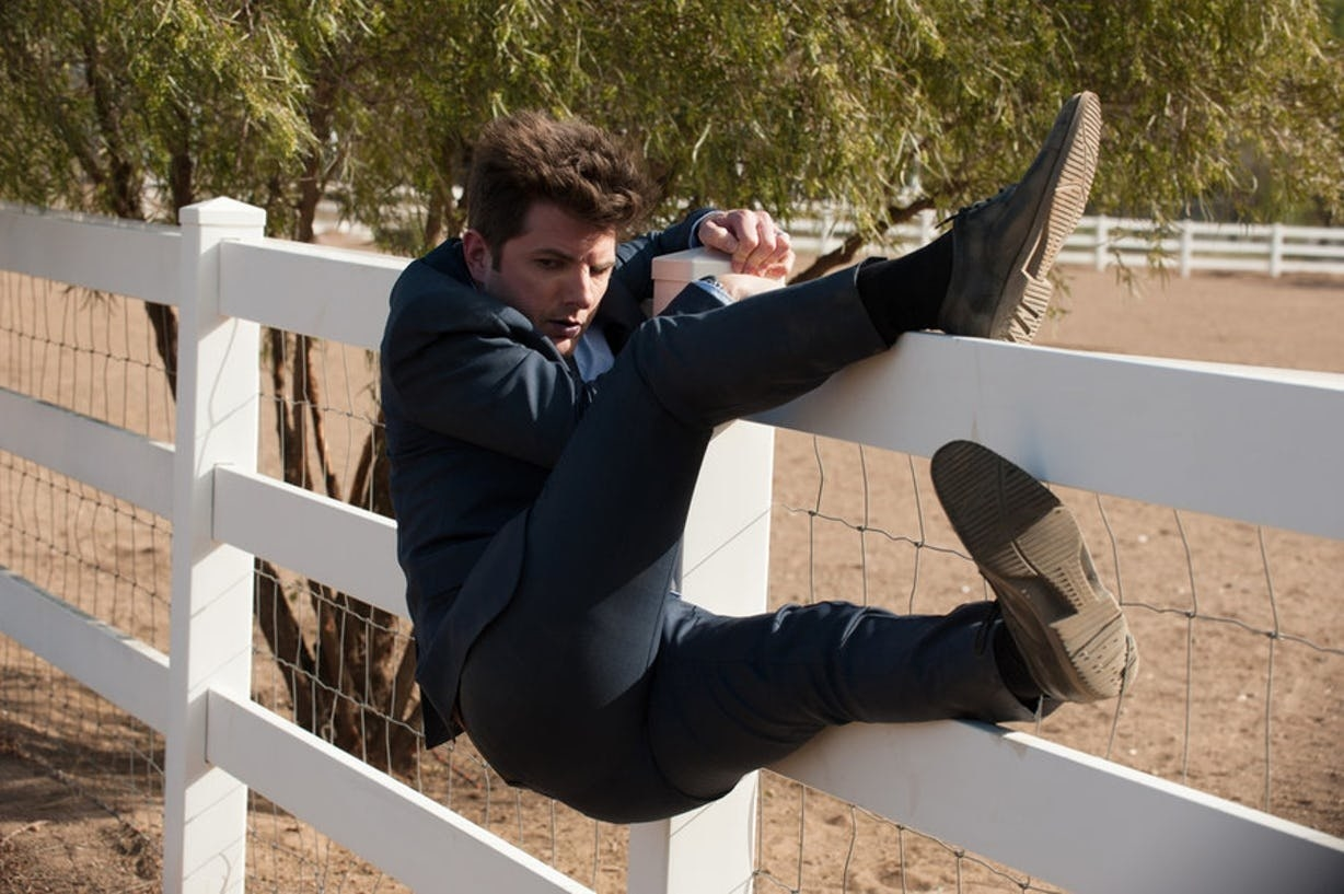 Ben Wyatt is dressed in a suit and clings to the side of a short fence in an attempt to climb over it.