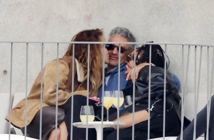 RIta, Taika, and Tessa embracing at a table