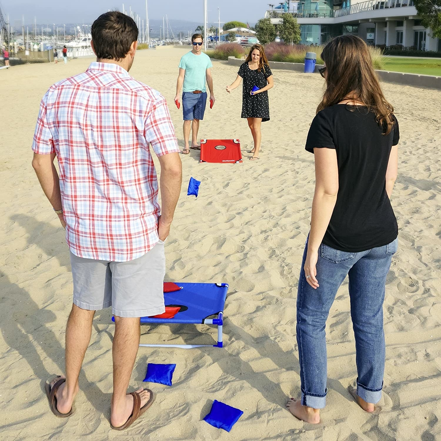 A group of people playing the cornhole game at the beach