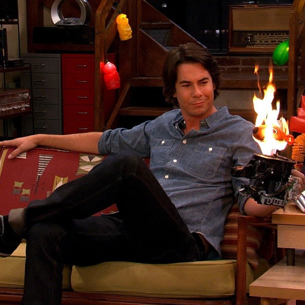 Spencer Shay sits on the couch, amused as he holds a squirrel sculpture made from camera parts which has inexplicably lit on fire