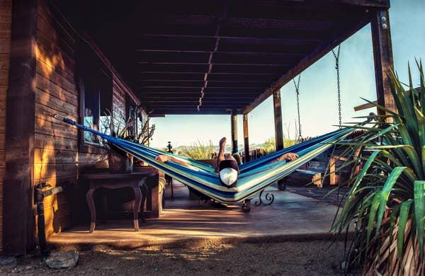 Person relaxing in a hammock outside a cabin in Joshua Tree