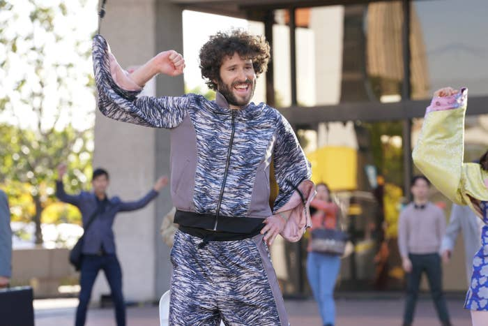 Dave in a stripy patterned sweatsuit, smiling, doing a dance move with one fist in the air