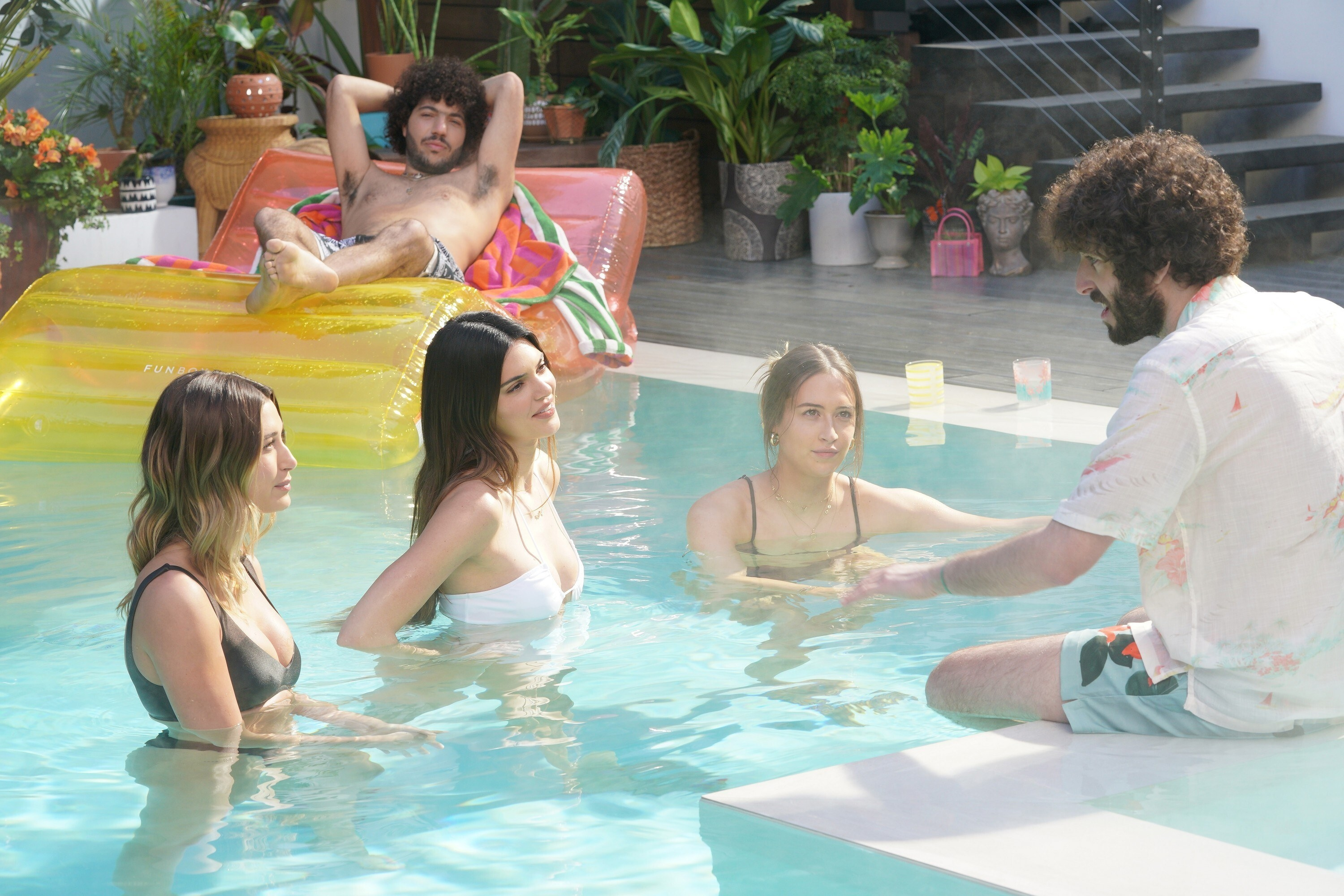 Hailey Bieber, Kendall Jenner, and Elsie Hewitt in a pool with Benny Blanco, lounging on a float in the back with Dave sitting on the ledge