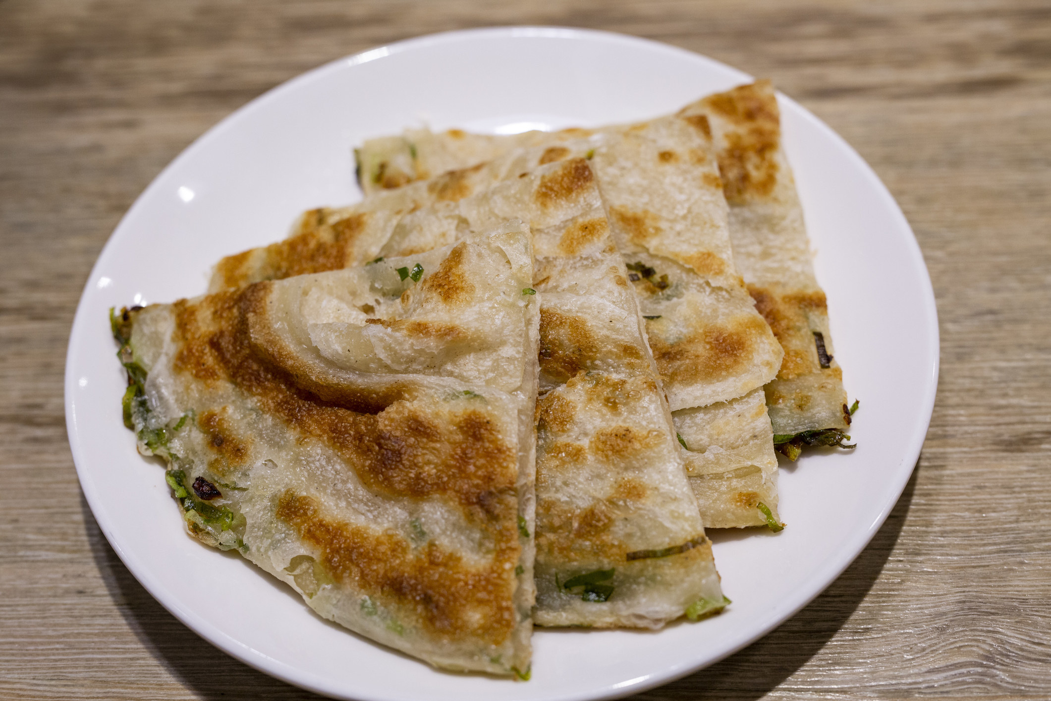 A plate of scallion pancakes sliced into triangles