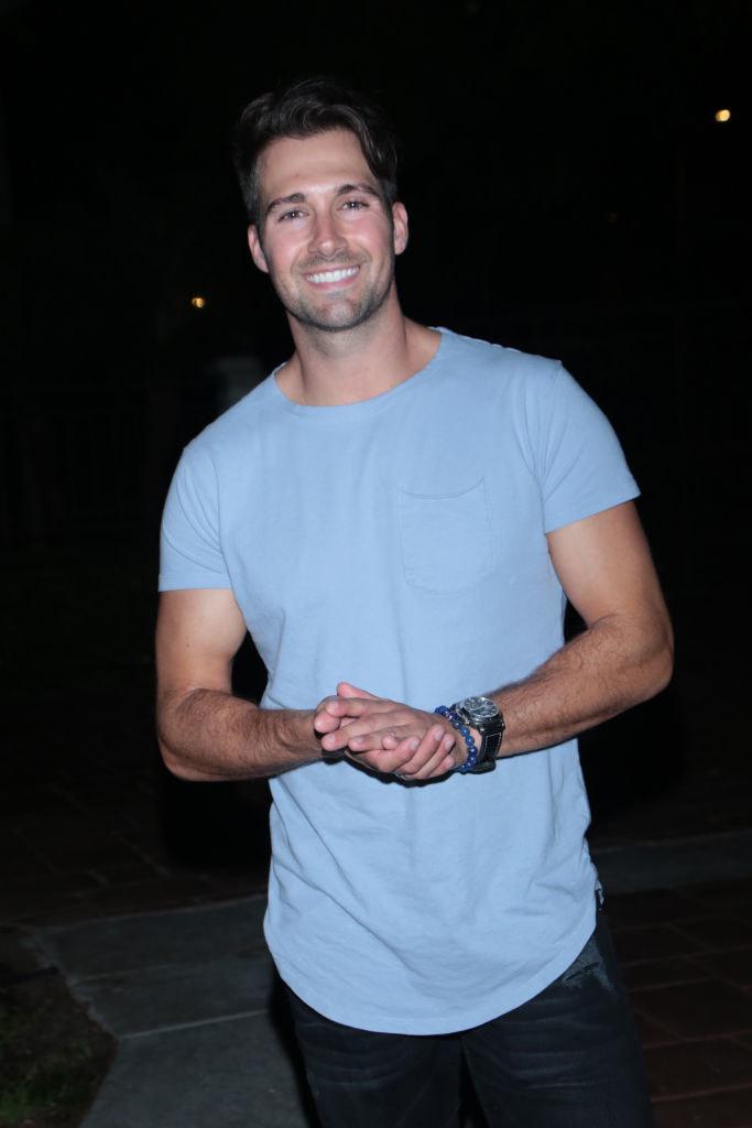 James Maslow walking down a sidewalk at night smiling at the camera