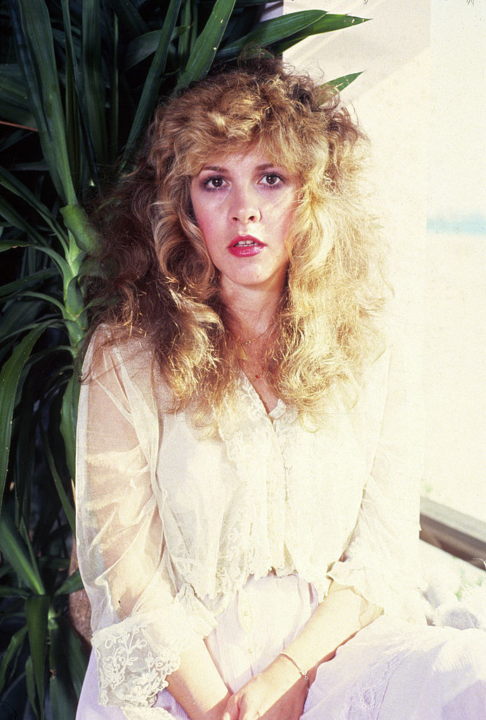 Stevie Nicks posing for a portrait in a long, lace gown in 1981