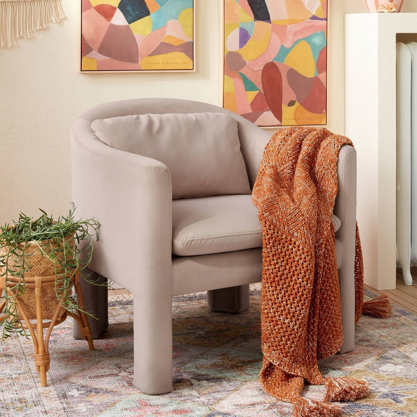 a light pink accent chair with an orange throw blanket