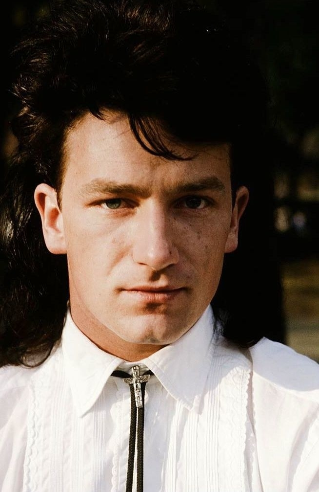 Bono posing for a portrait in a bolo tie with long, dark hair in 1983