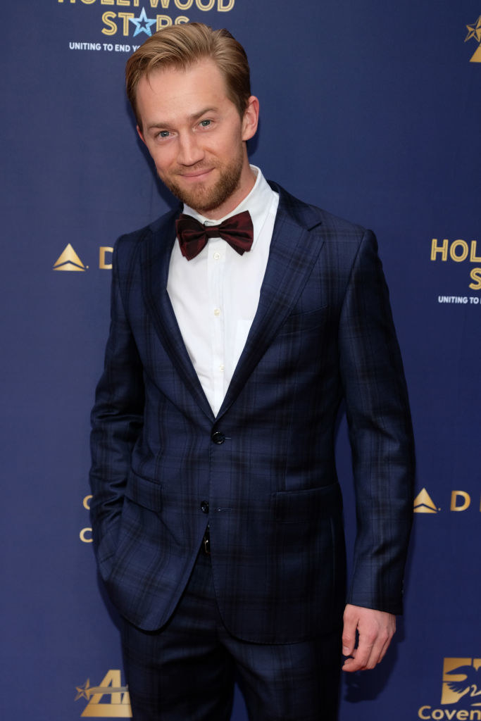 Jason Dolley in a suit on a red carpet