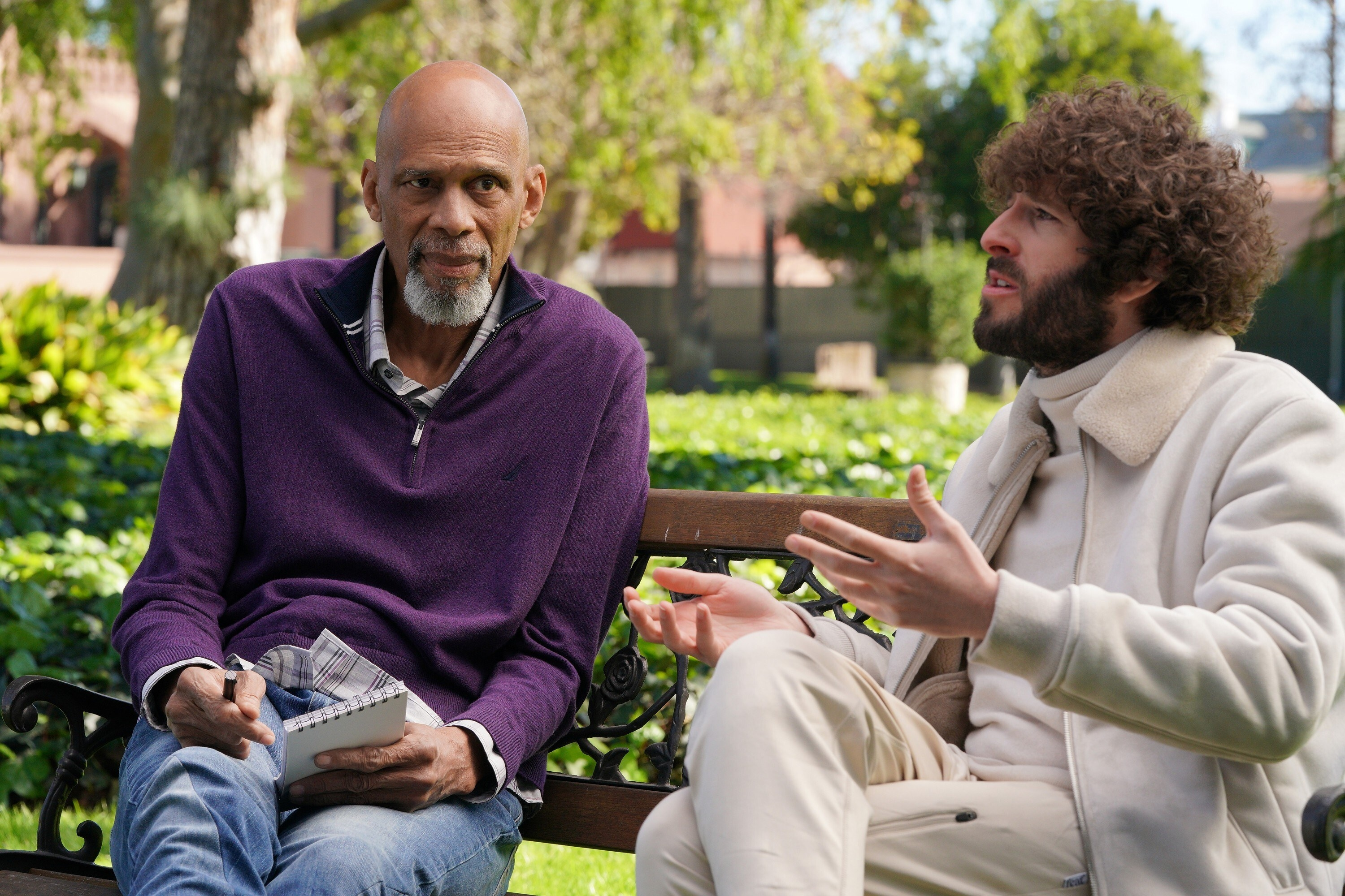 Kareem Abdul-Jabbar in sweater and jeans with notepad sitting with Dave in sweatsuit on a bench outside