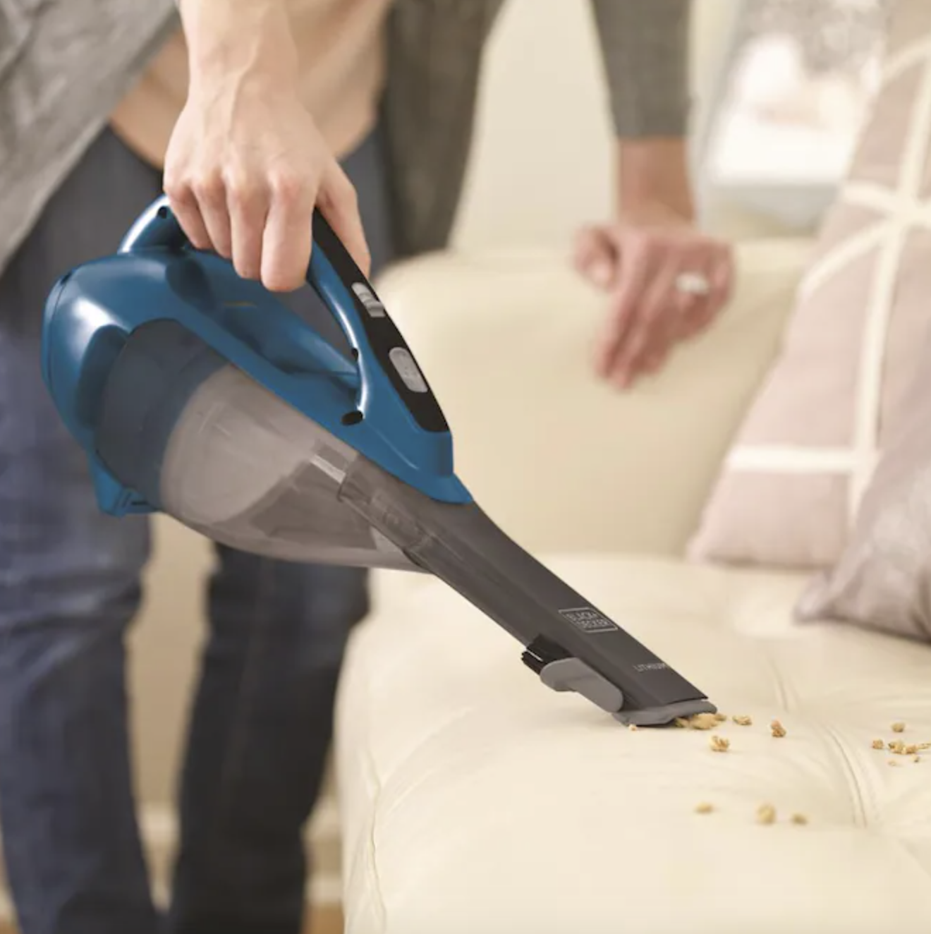 Model using Black and Decker handheld vacuum on couch