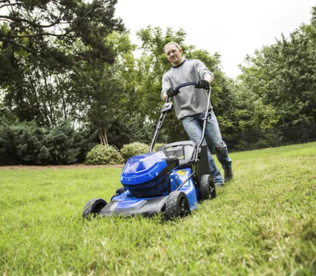 Model using cordless lawnmower on grass