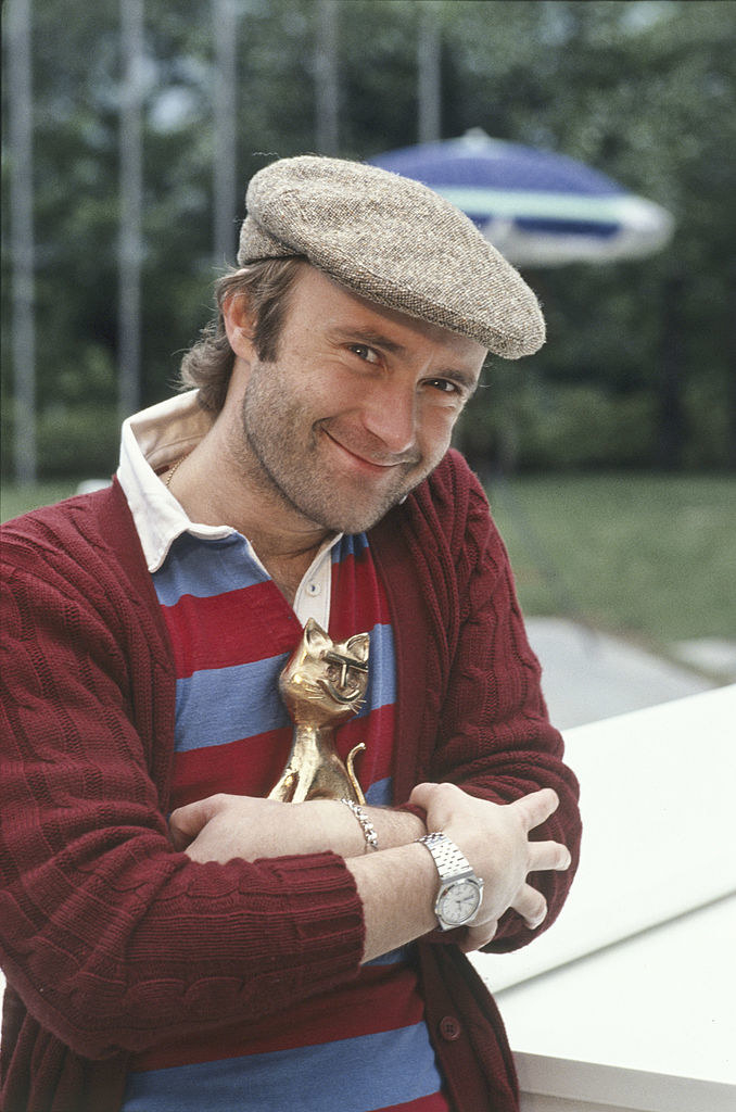 Phil Collins holding an award while wearing a sweater and cap in 1981