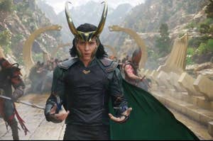 Loki on a bridge wearing a cape and horns