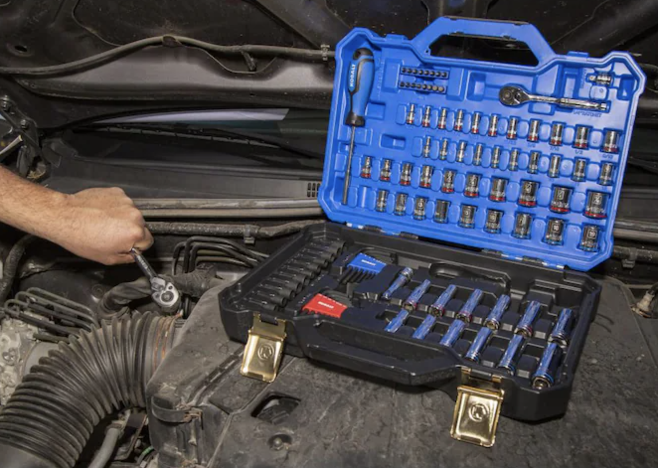 Toolkit placed inside hood of car with model using tools on car