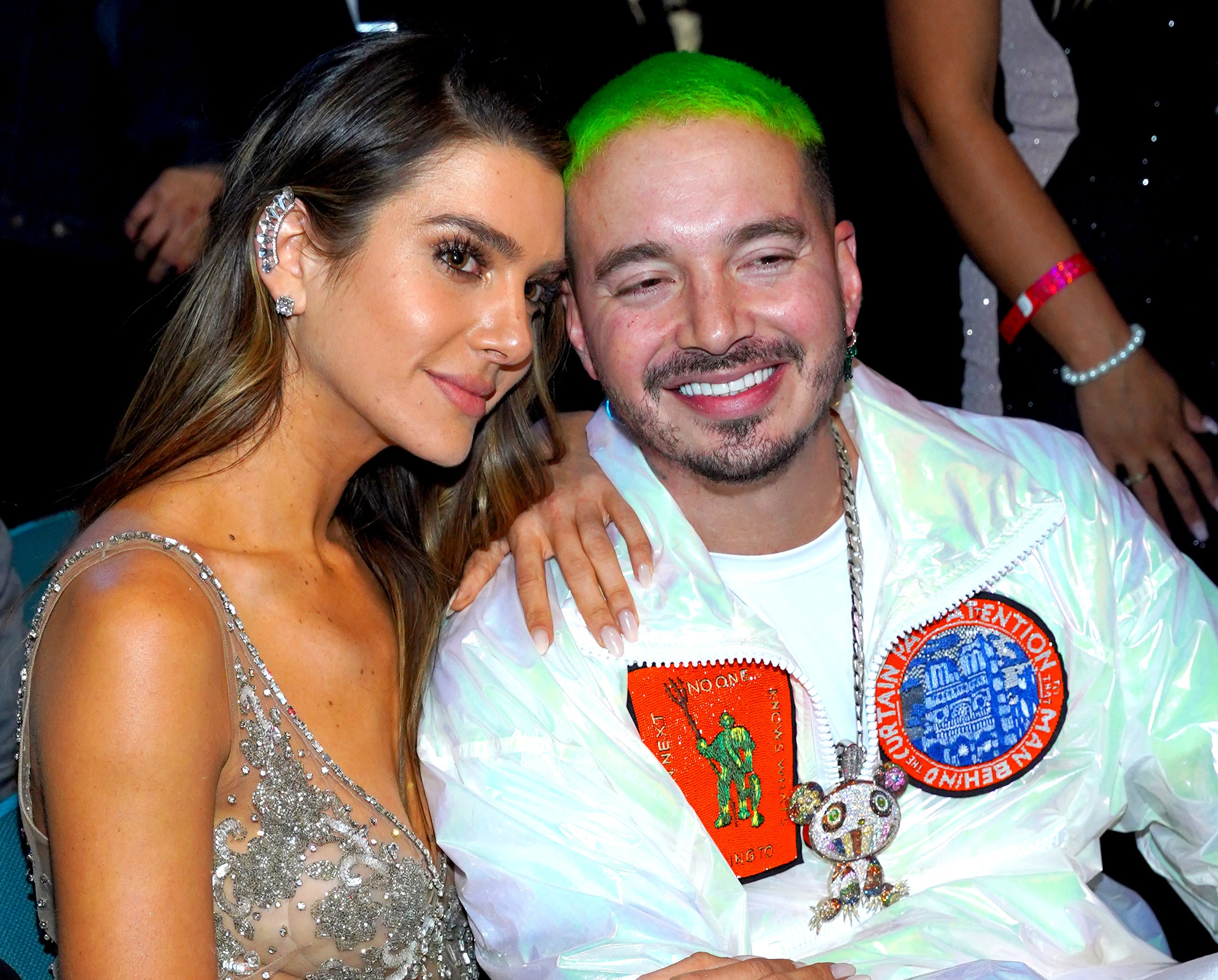 J Balvin and Valentina smile while sitting next to each other at an event