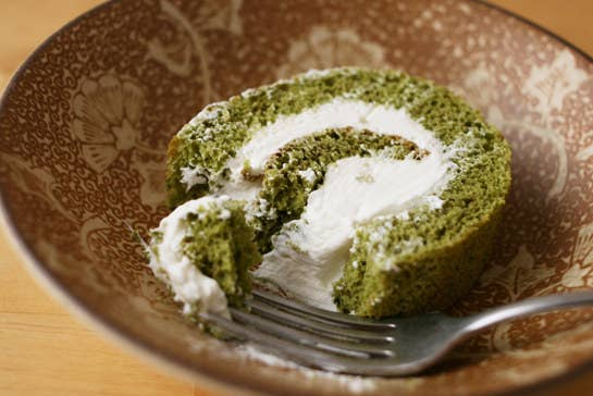 Fork in matcha swiss cake roll with a heavy serving of cream filling.