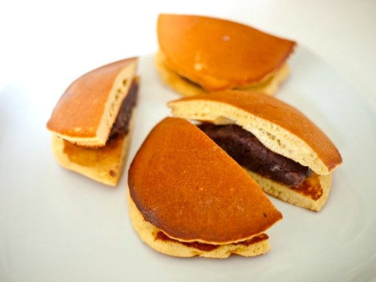 Two halved dorayaki sandwiches, showing their red bean fillings.