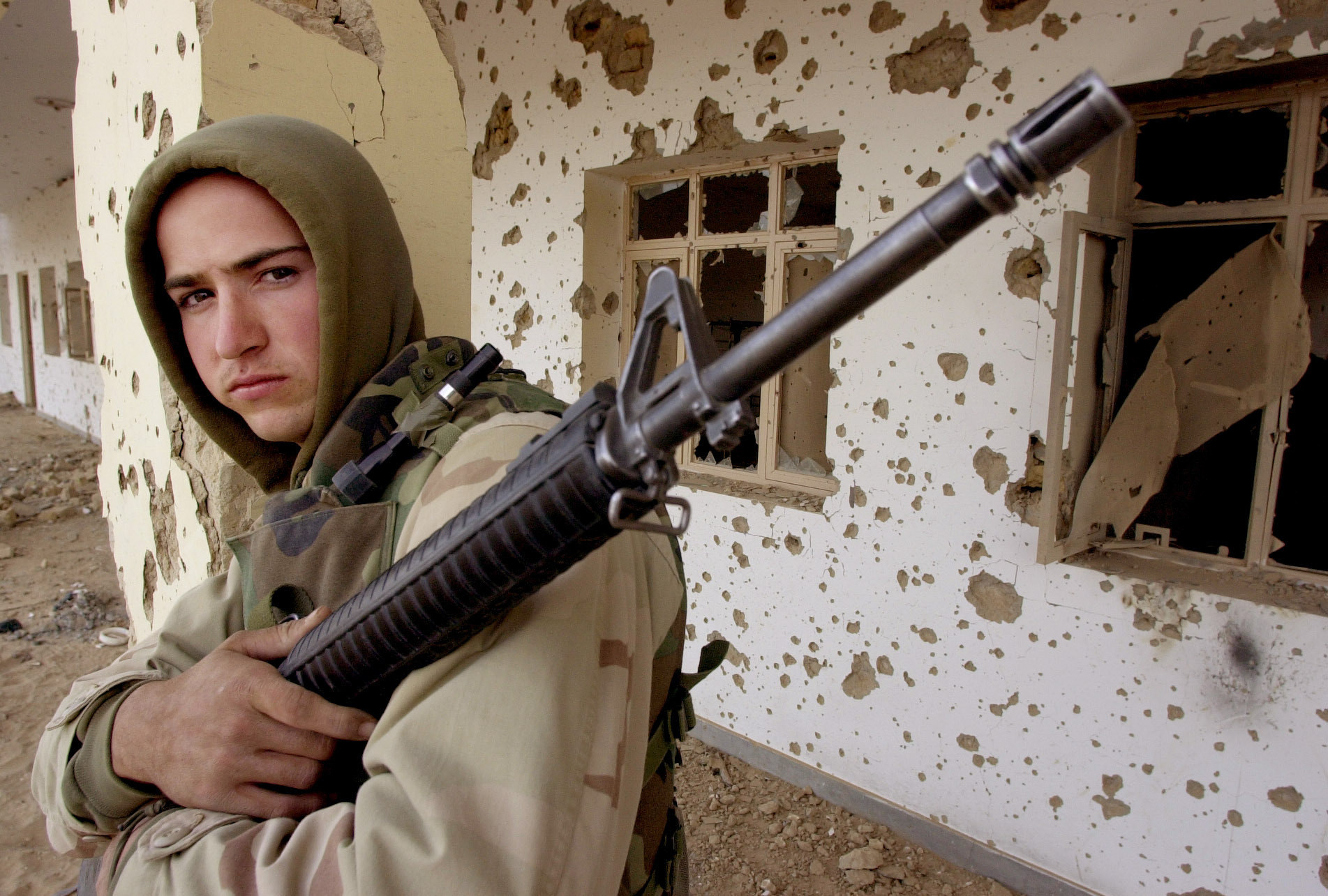 A young man stands with a gun in front of a bullet riddled building in Afghanistan
