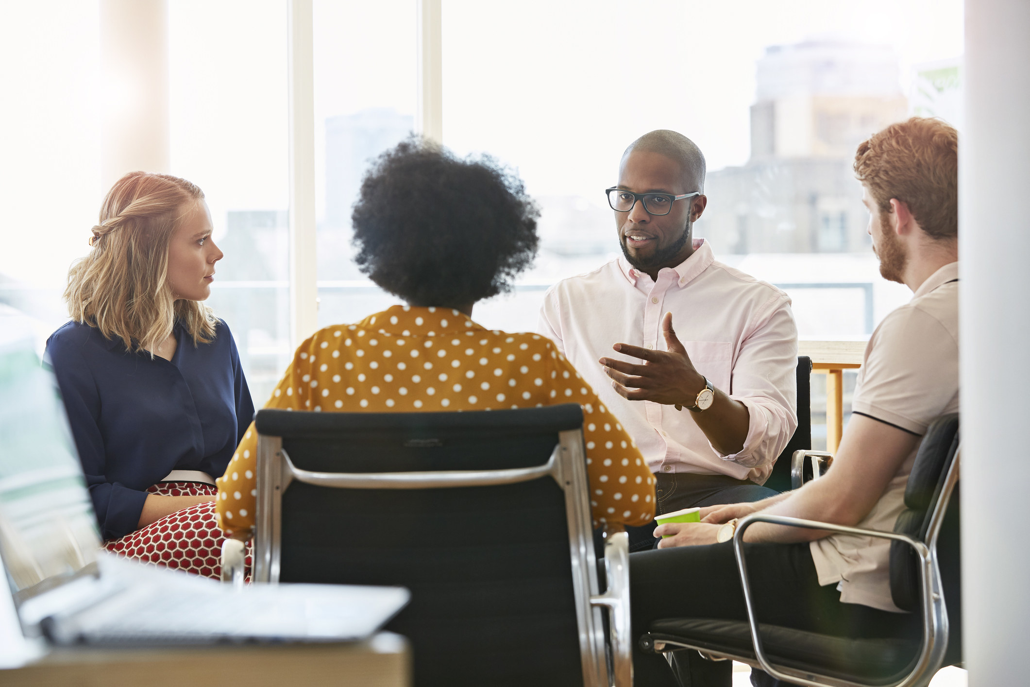 Four people having a conversation in an office