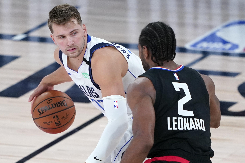 Luka Doncic dribbles a basketball while Kawhi Leonard defends