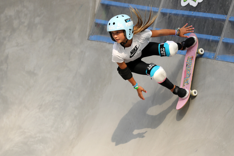 Sky Brown on a skateboard going down a skate park pool