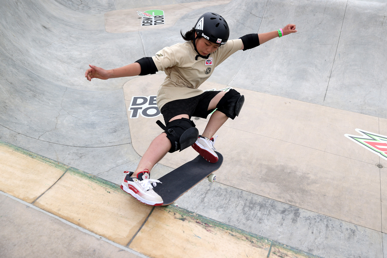 Misugu Okamoto grinding her skateboard on edge of skate park pool