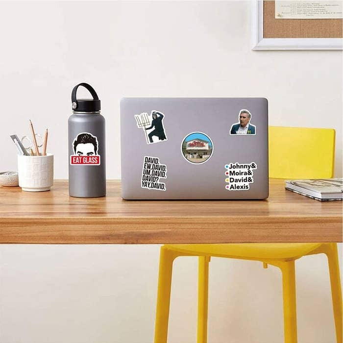 A laptop on a desk covered with stickers