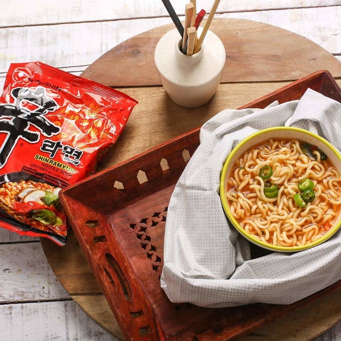A bowl of soupy ramen with chopsticks and an empty packet of red Nongshim ramyun kept on the side.