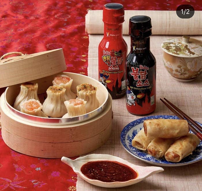 Two dishes of dimsums and spring rolls along with a sauce bowl full of hot chicken flavour sauce and two bottles of the spicy sauce.