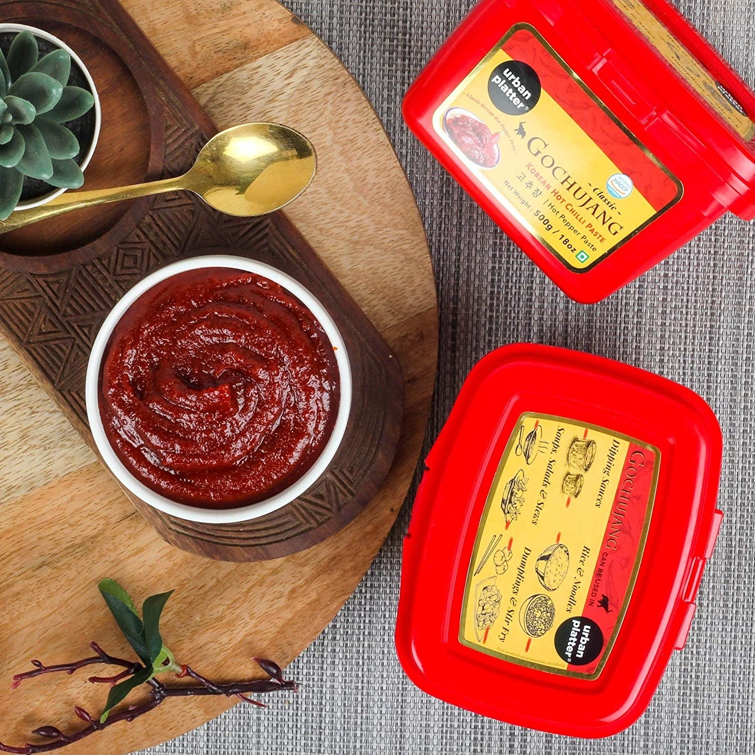 Two boxes of 500gm red gochujang paste kept alongside the sauce in a dipping bowl.
