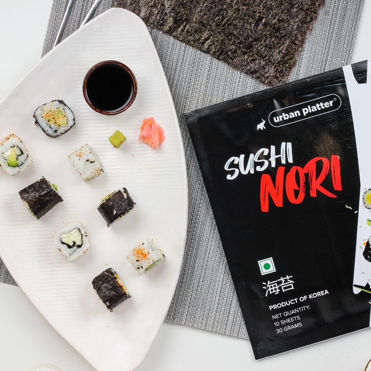 A pack of seaweed sheets set alongside a plate of sushi/kimbap wrapped in seaweed sheets.