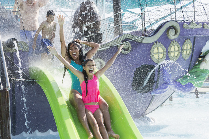 Two young people going down a water slide with their arms raised and wide smiles in their faces