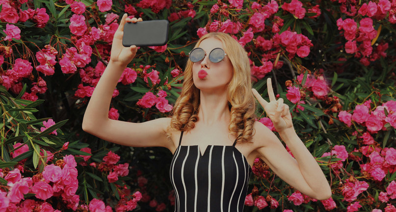 A person taking a selfing in front of a wall of flowers
