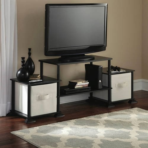 The center in black holding a TV and two white storage bins