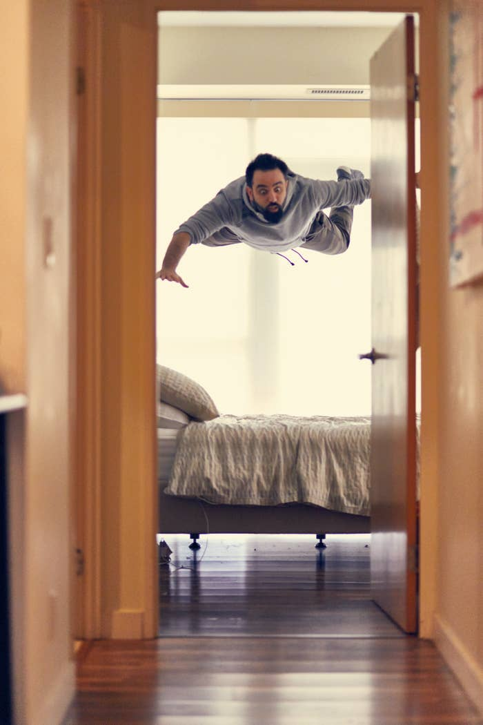 Through a doorway, a man is frozen in the air over top of a bed