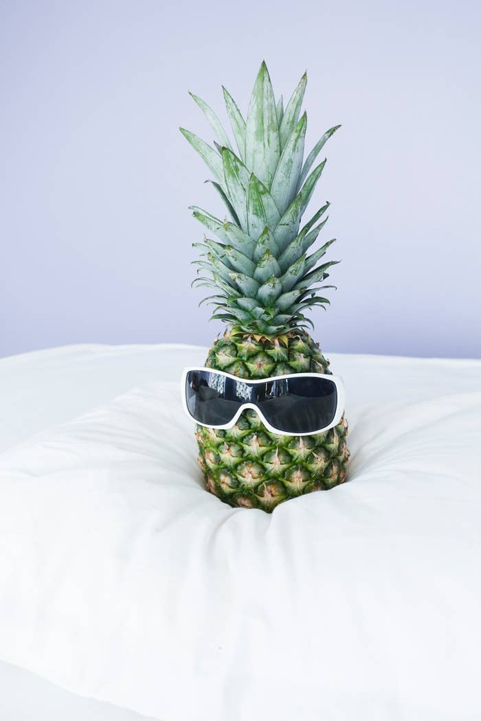 A pineapple is sitting on a white bed wearing white sunglasses