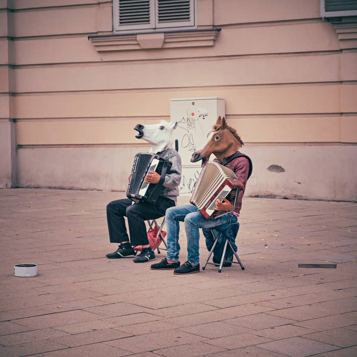 Two people in horse masks are both sitting in chairs on the street playing the accordian